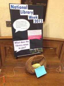 National Library Week display on a table at the Robbins Library, with a poster and a basket for comment cards