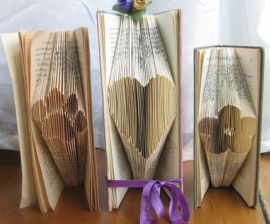 Three examples of book folding: a paw print, a heart, and a flower