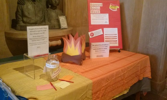 Banned Books Week display table with poster, fake flames, ALA statement, and Books Change Lives jar