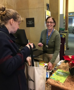 Senior Library Assistant Sheila Berry Helps a Library Visitor Renew Books
